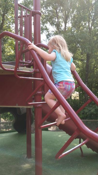 Hier erklimmt die Kleine eine der Leitern zu einem riesigen Kletterturm mit unzähligen Rutschen.
